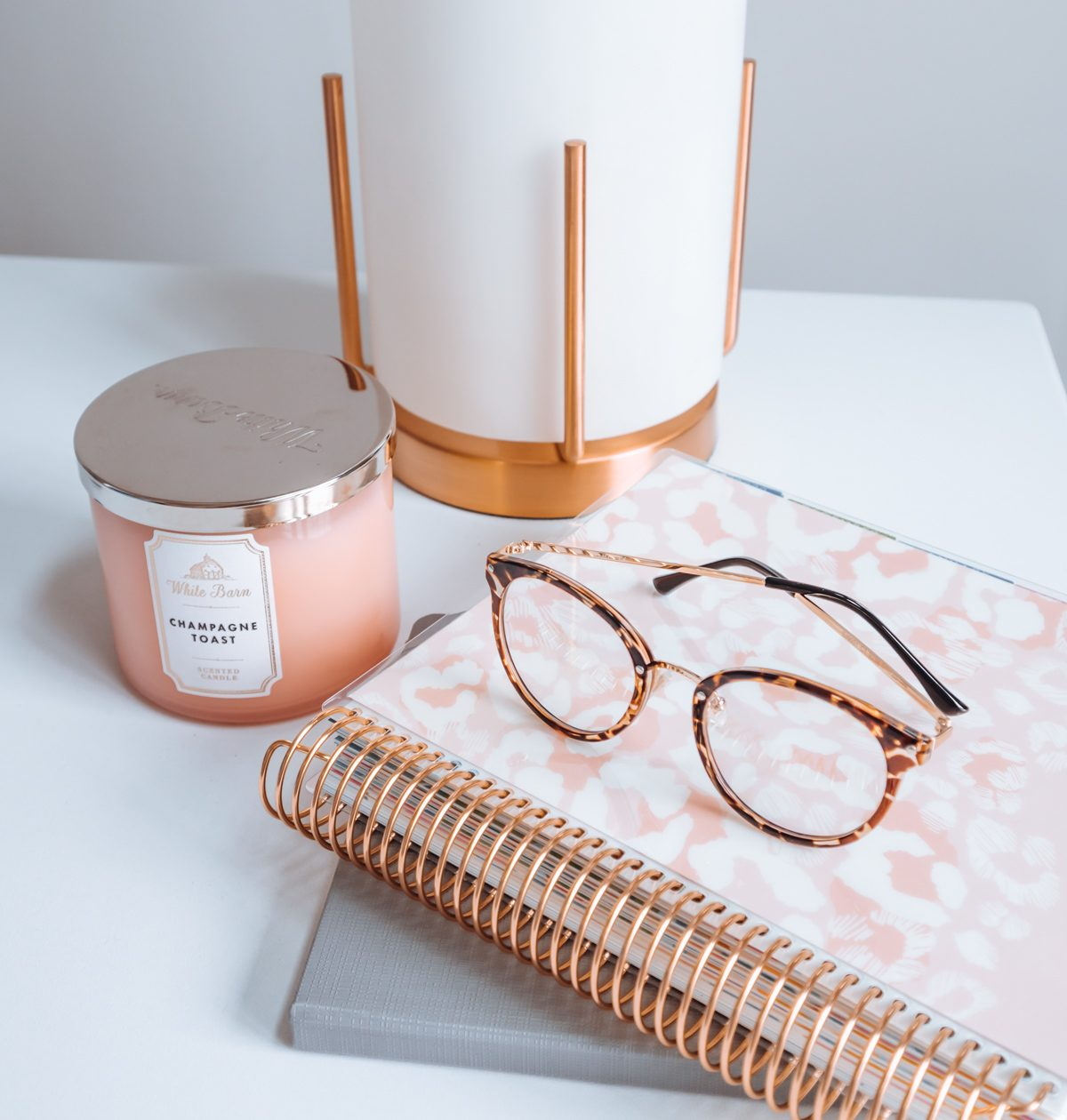 A pair of Amazon blue light glasses on top of a planner and notebook.