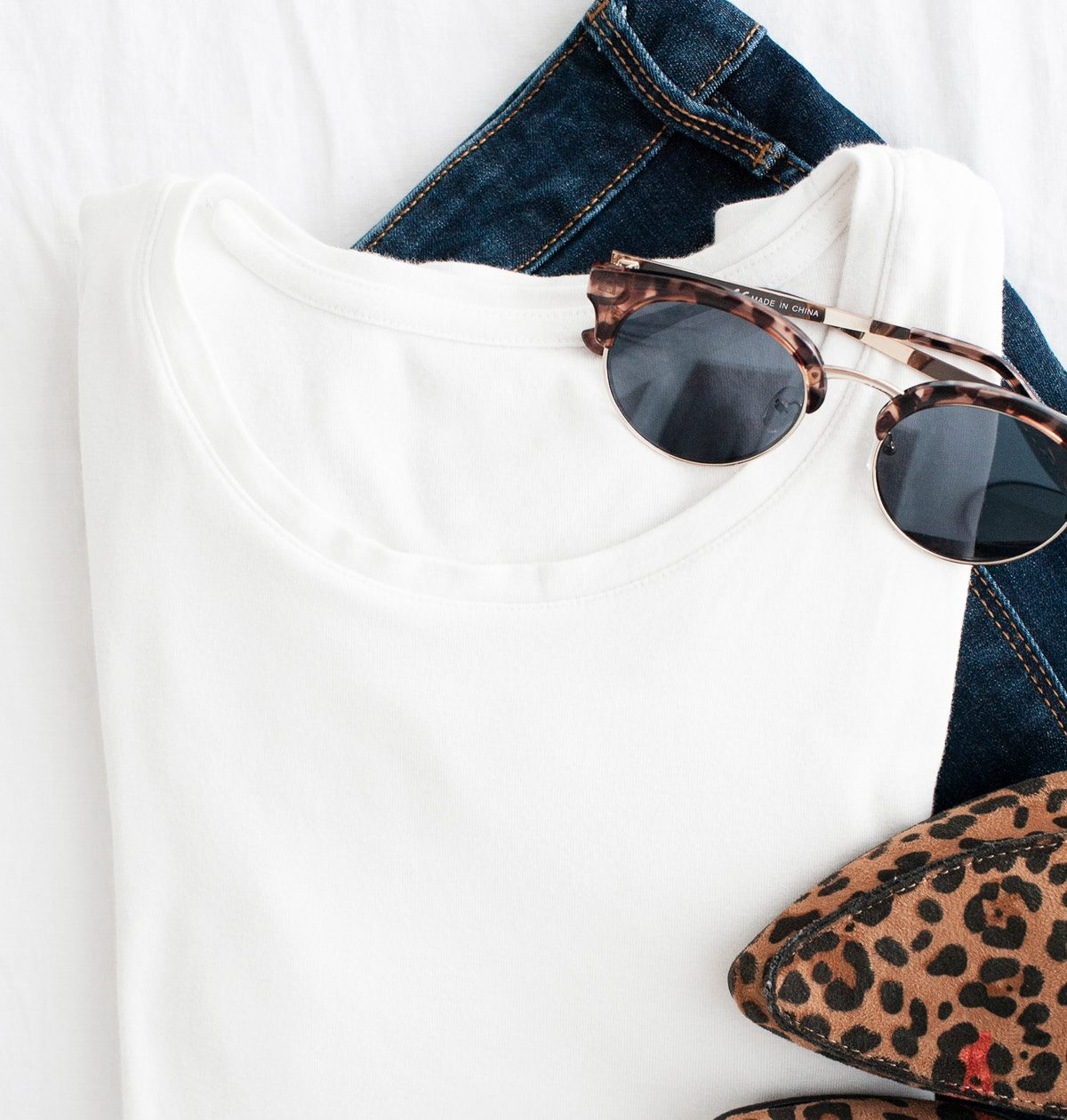 A simple outfit consisting of jeans, a white t shirt, sunglasses, and leopard print mules.