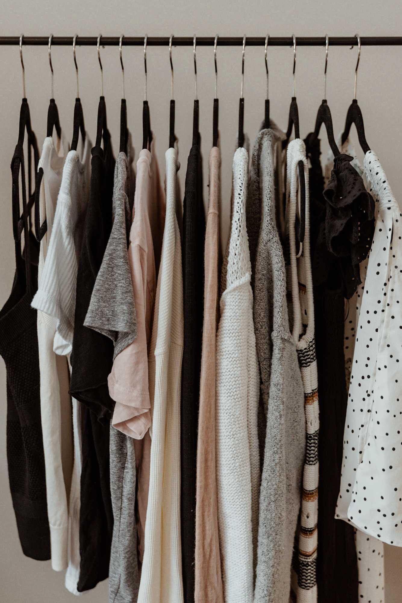 A sample of neutral-colored capsule wardrobe basics including tops, bottoms, dresses, and jumpsuits.