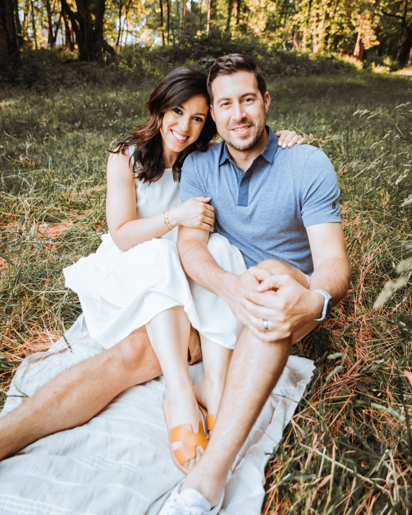A picture of a couple sitting on a blanket in the woods.