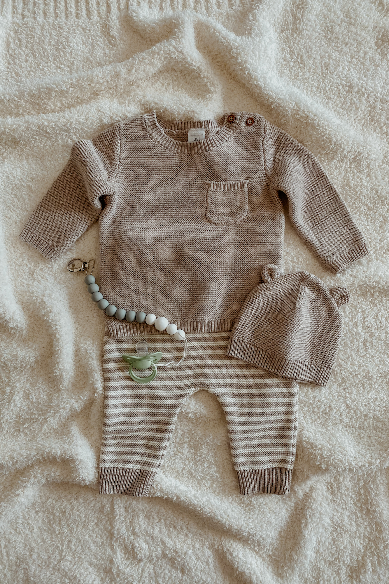 A knit gender neutral baby outfit flatlay.