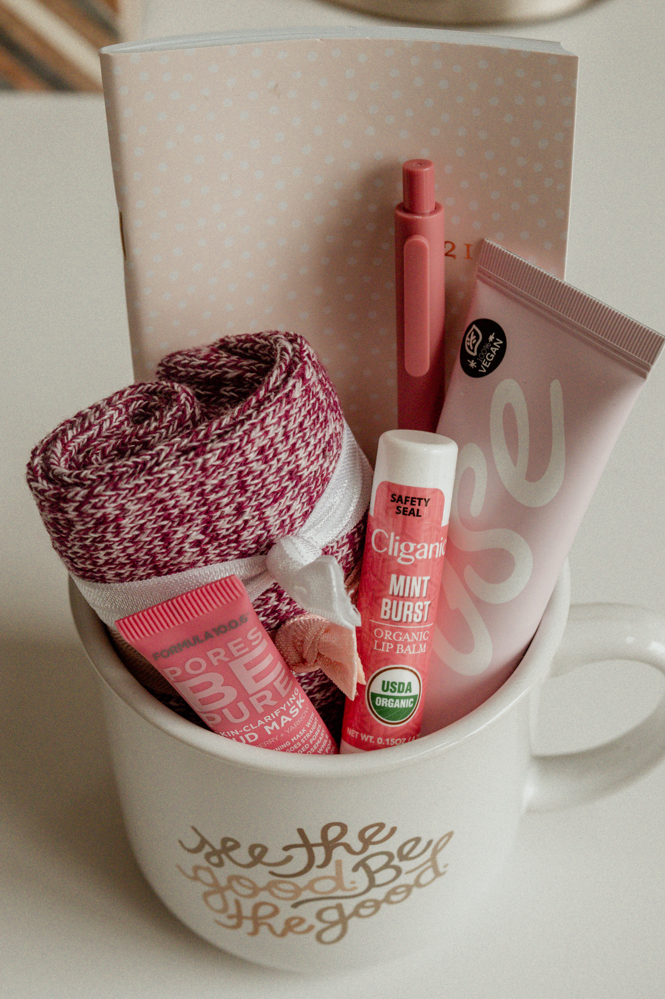 A filled mug gift idea for women including face masks, hair ties, hand cream, socks, and more.