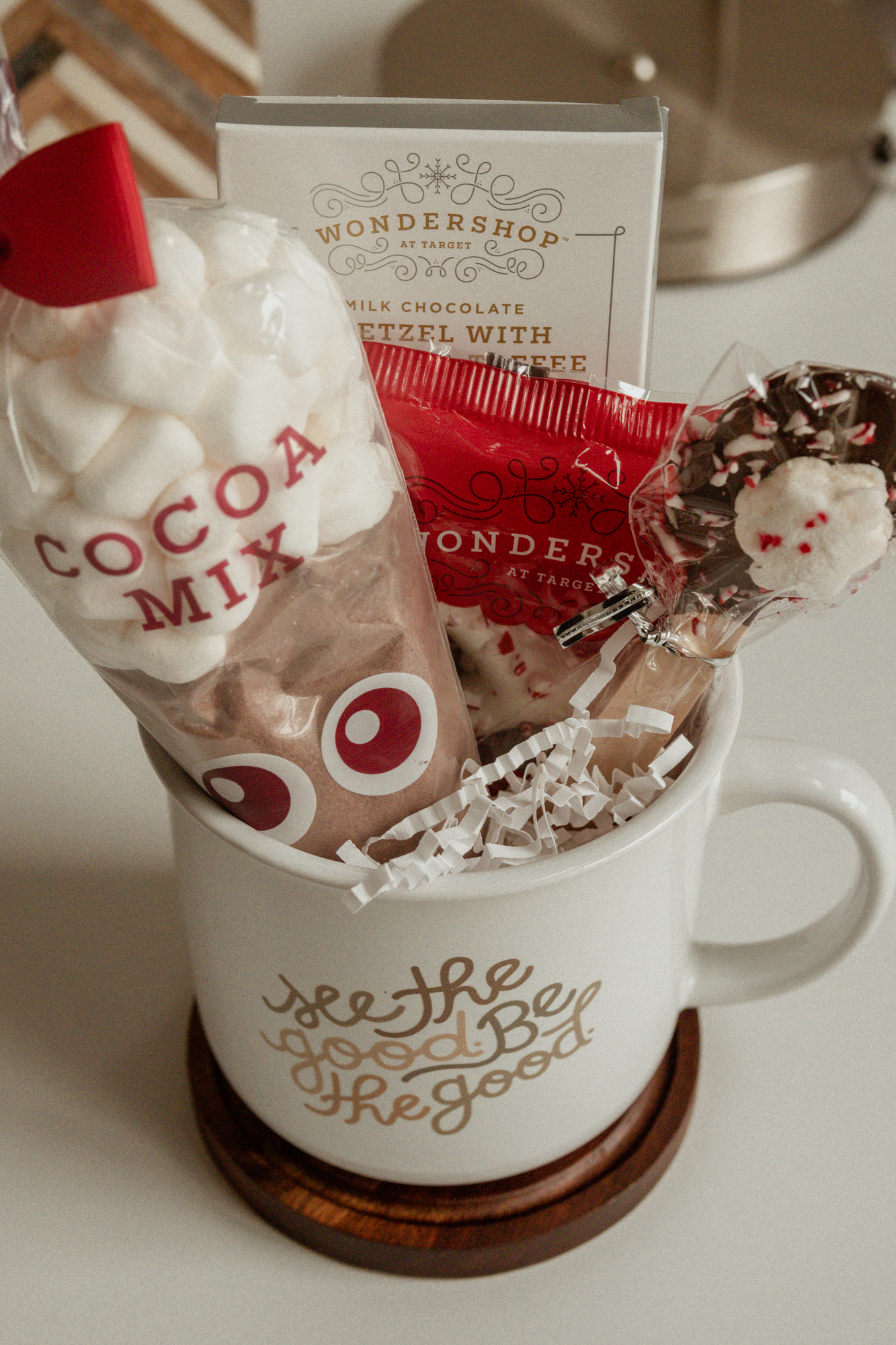 A filled mug gift idea for Christmas including hot cocoa supplies.