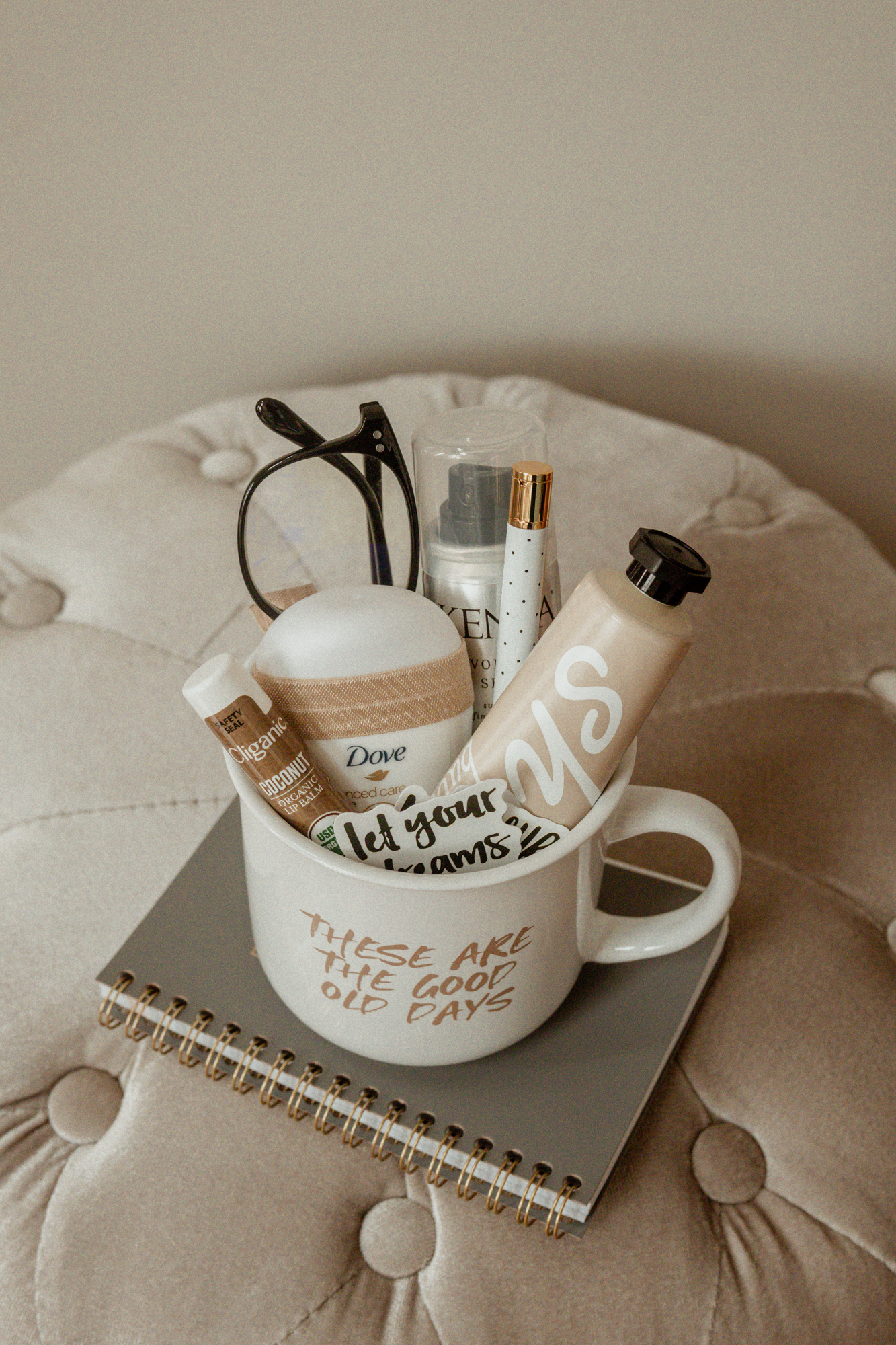 A filled mug gift idea for friends including travel-sized beauty products, blue light glasses, and motivational stickers.